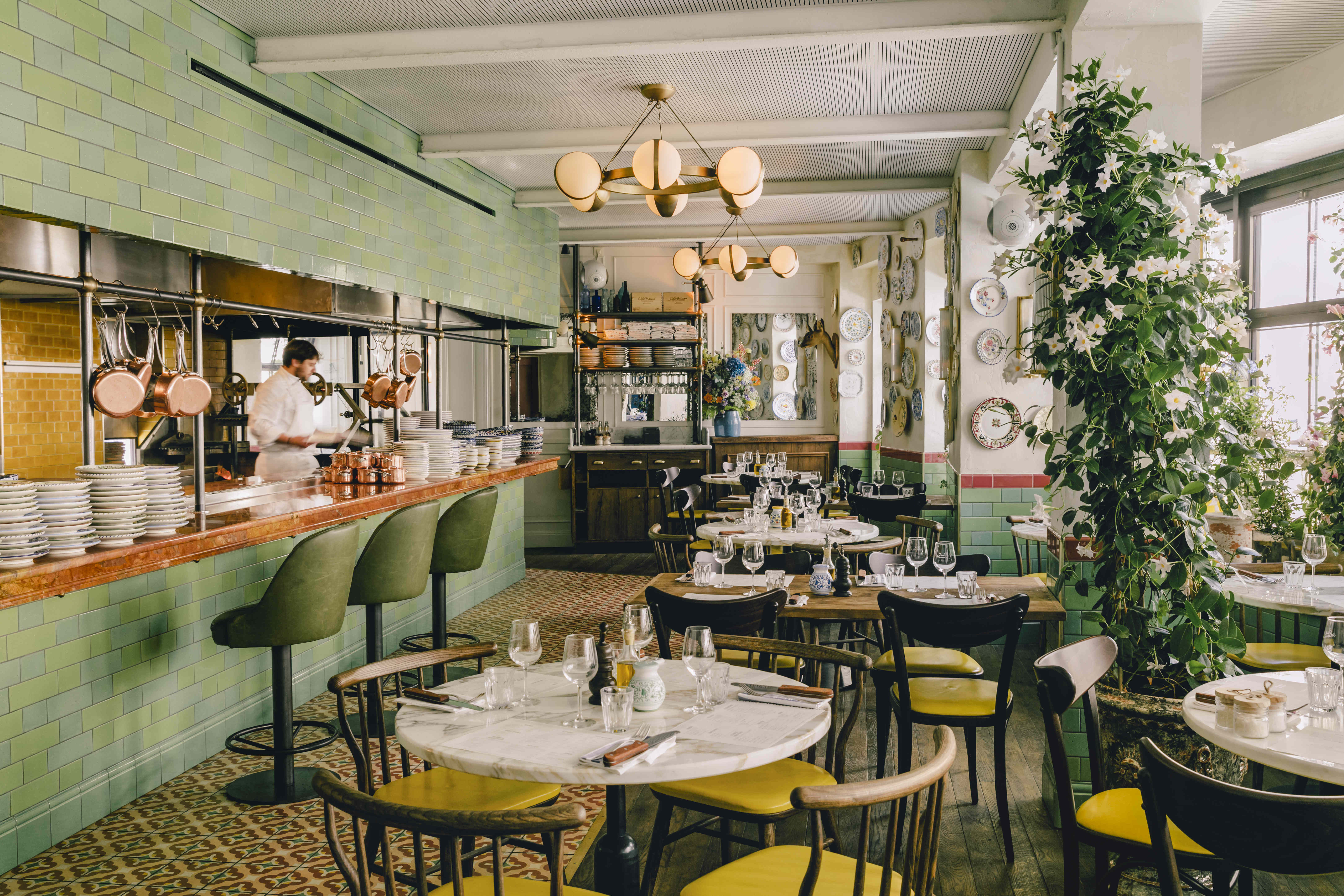 A green and plant-filled interior of a French restaurant.