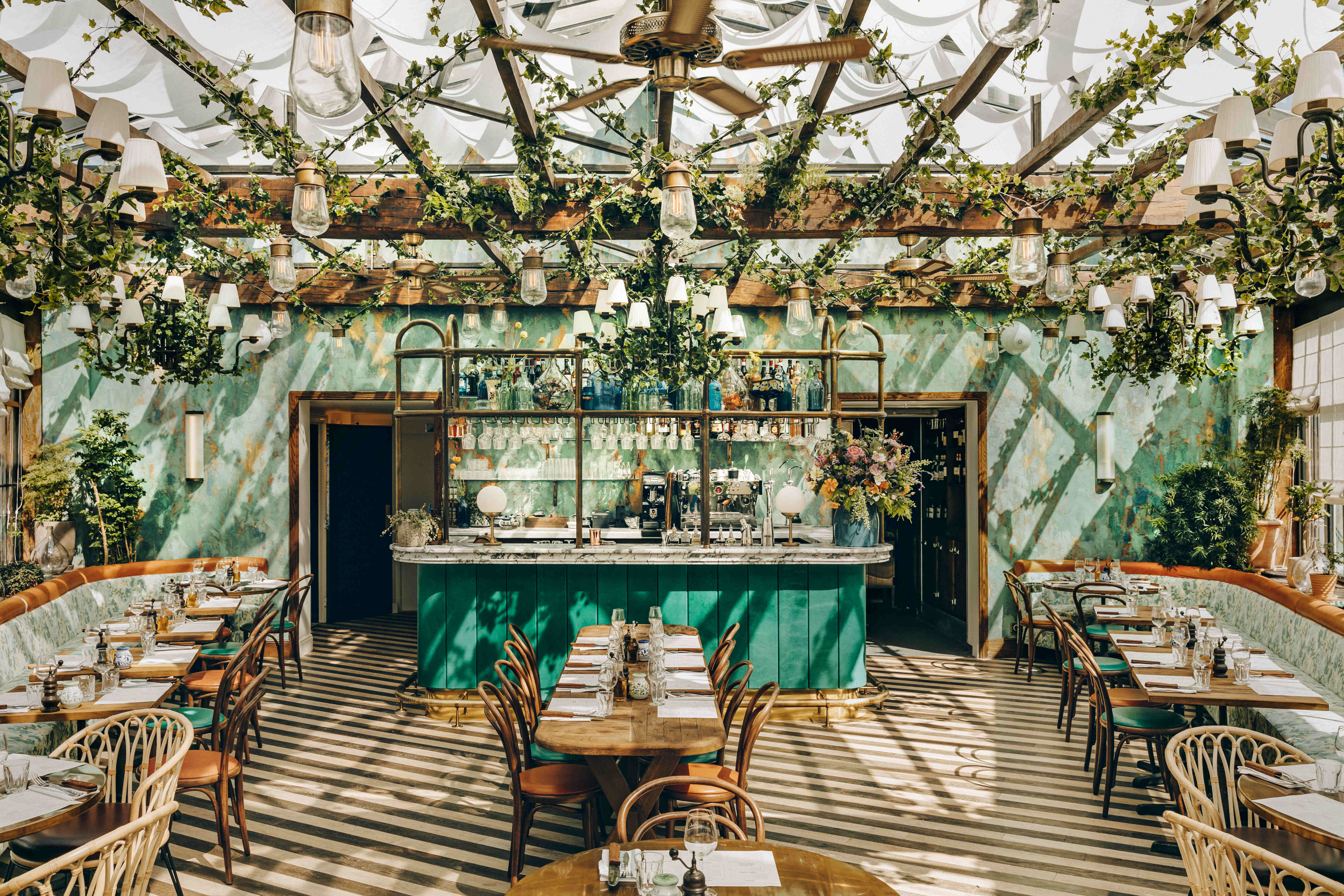 The interior of the restaurant is filled with plants.