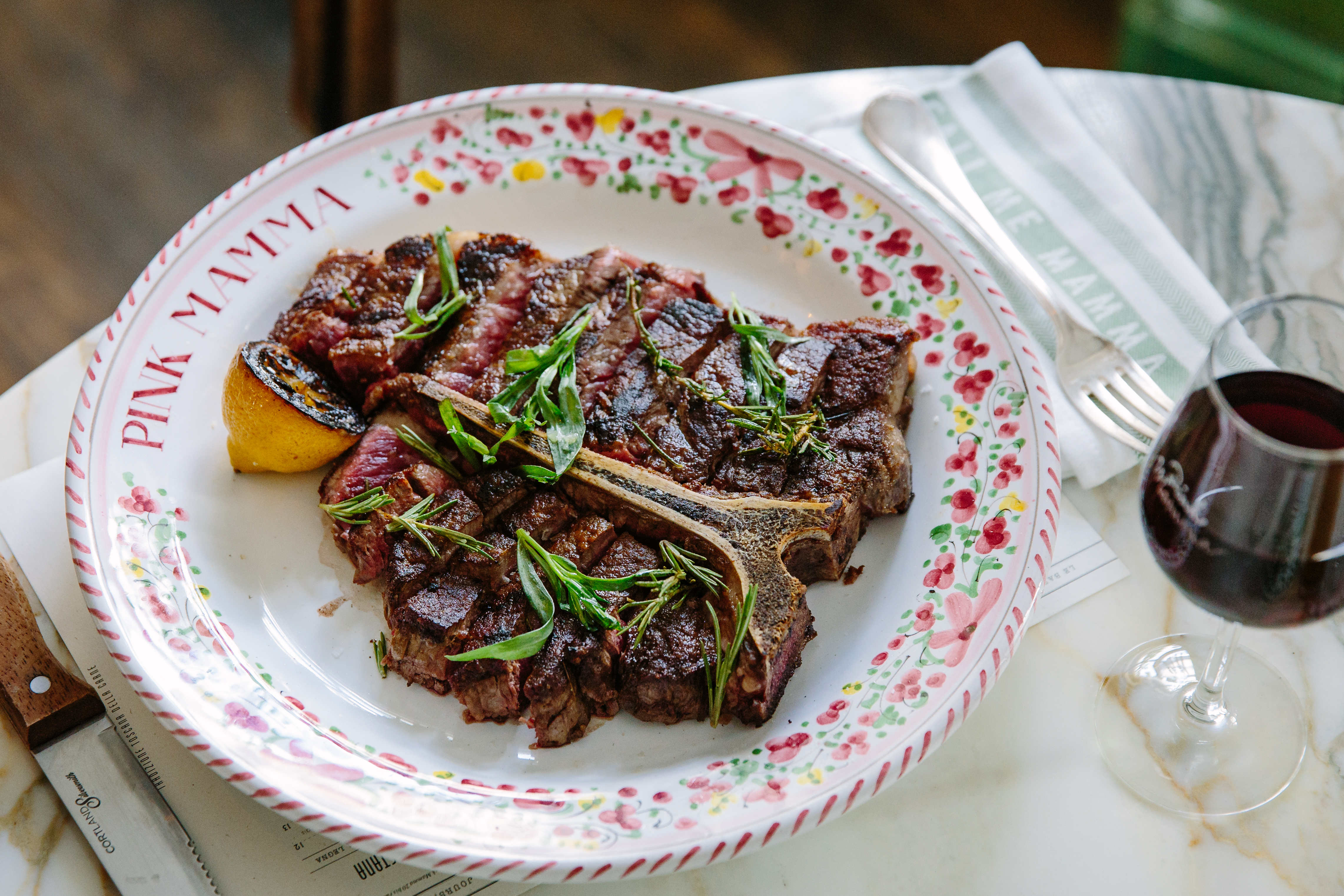A succulent steak sits on a custom plate with a glass of red wine.
