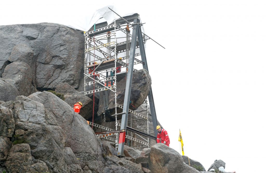 Workers lift the Trollpikken following a successful crowd funding campaign for its restoration.