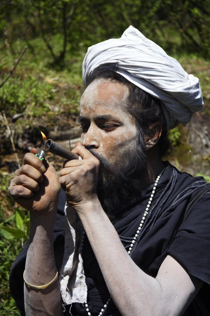 Portrait of Indian Sadhu lighting a charas chillum near Malana in Himachal Pradesh India