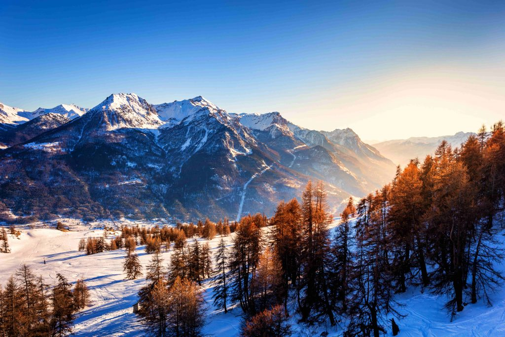 Frozen scene near a ski resort in the french alps just above Briancon in France, with blue sky before sunset in the golden hour over the mountain with fresh snow.