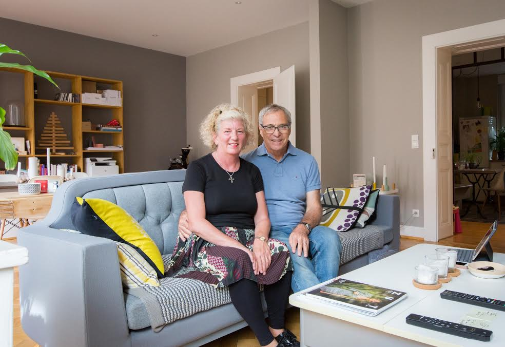 Debbie and Michael Campbell site on a couch in an Airbnb home.