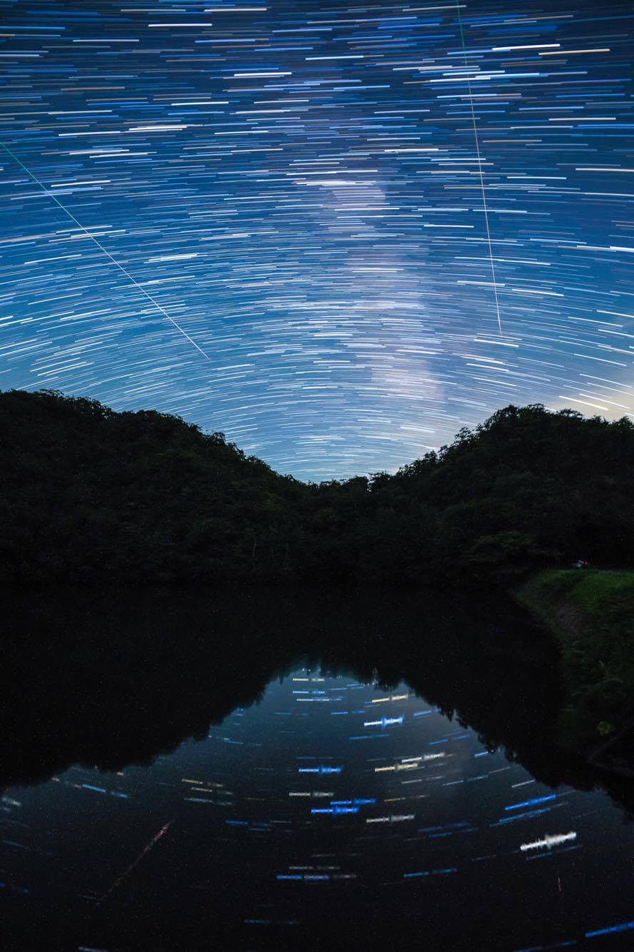 A long exposure shot showing star trails and Perseid meteors.