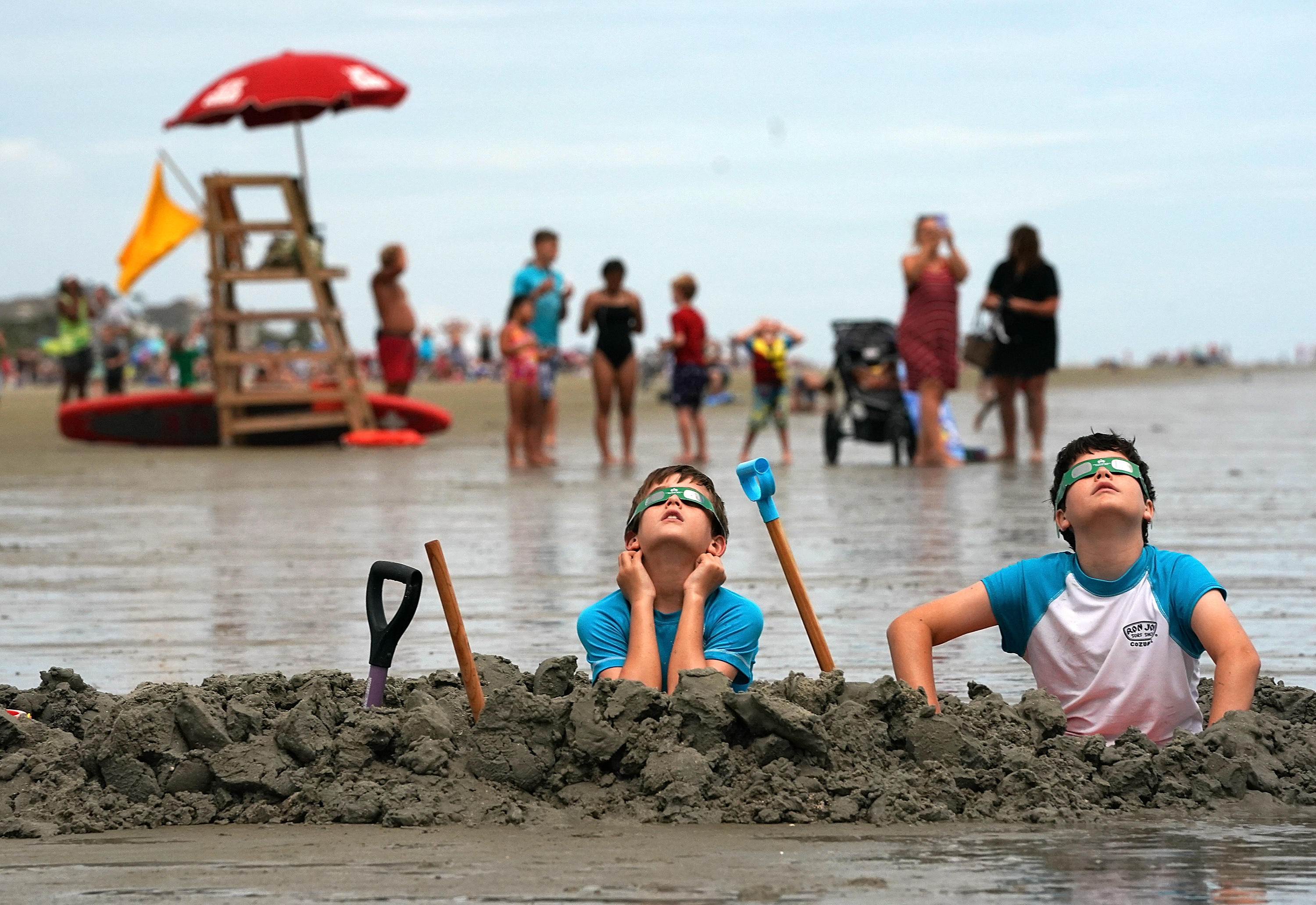Brothers Chris and Gabe Fabiano watch the first solar eclipse to sweep across the United States in over 99 years on the beach August 21, 2017 on Hilton Head Island, South Carolina.
