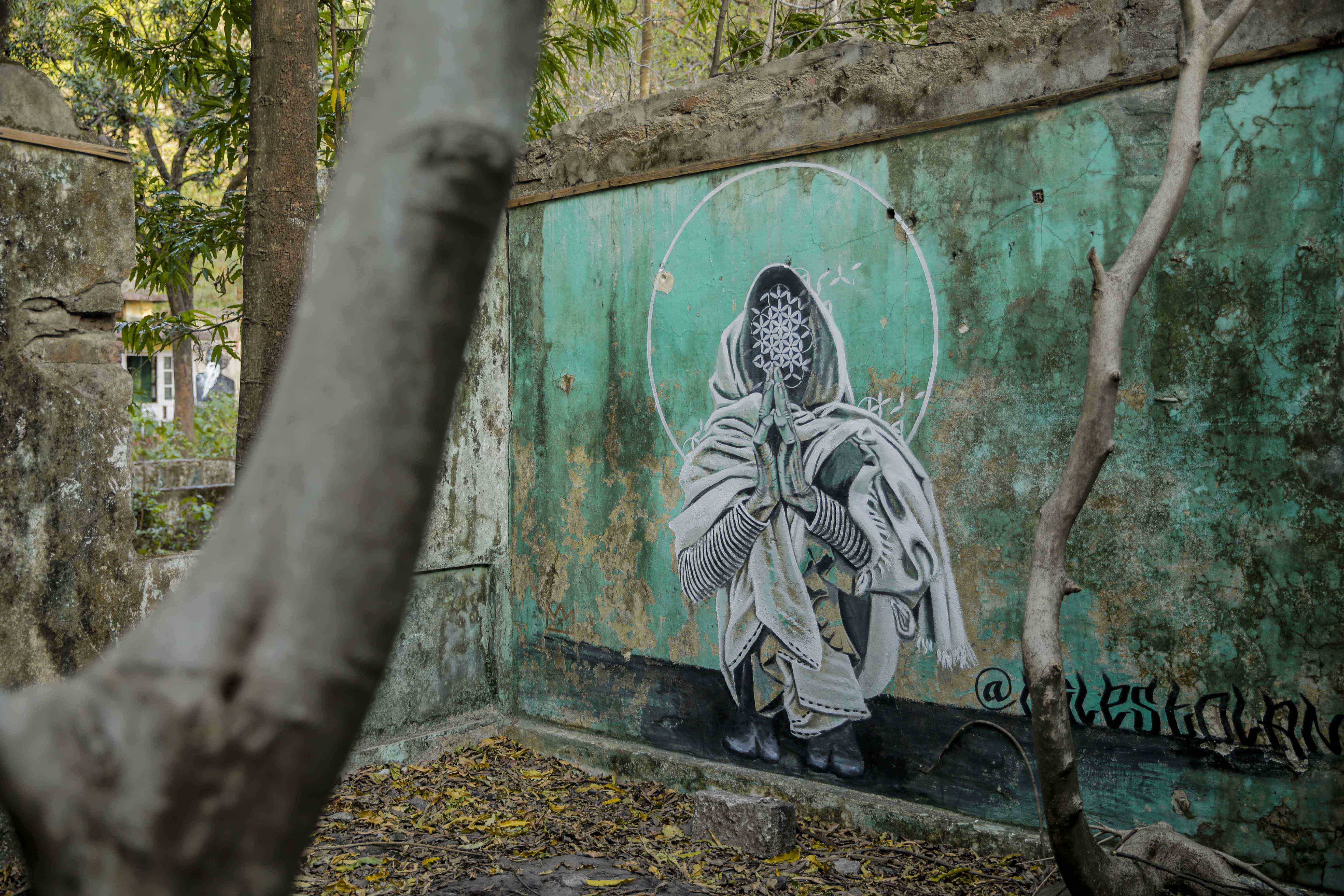 Artwork depicting someone meditating on the abandoned walls of the ashram