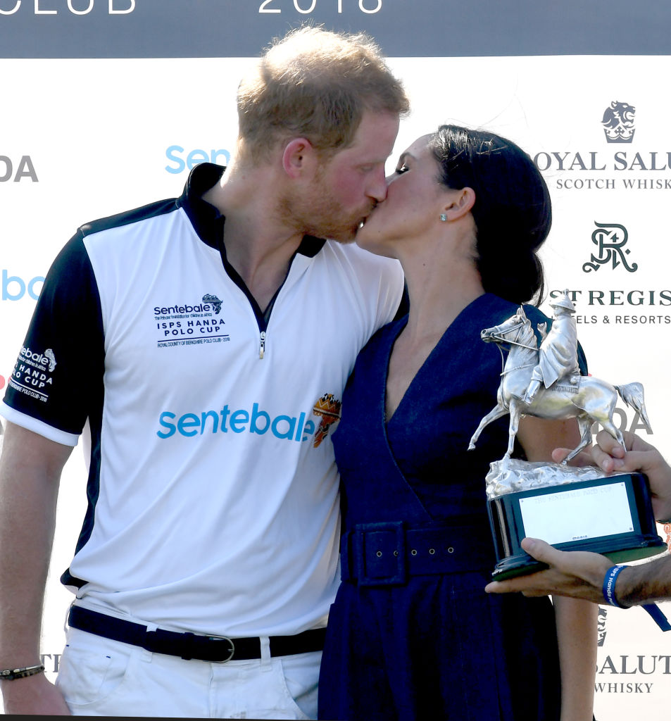 Prince Harry kisses his wife after winning cup.