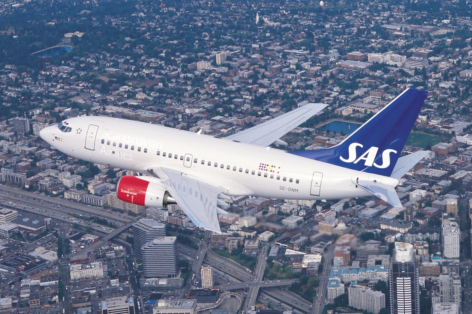 An SAS airplane in mid-air over a city.