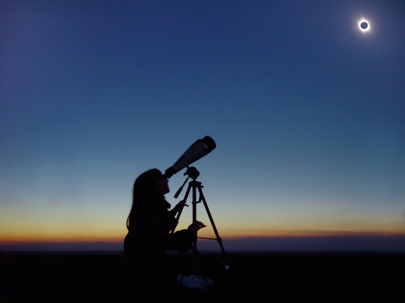 A woman watches a solar eclipse through a telescope