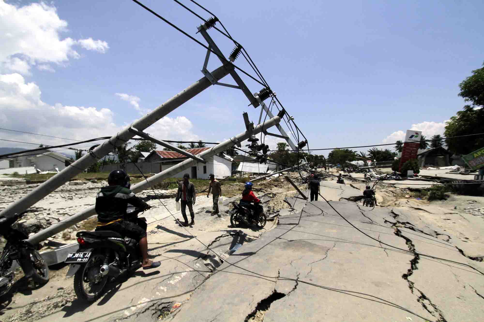 Palu residents help to clear a road following an earthquake